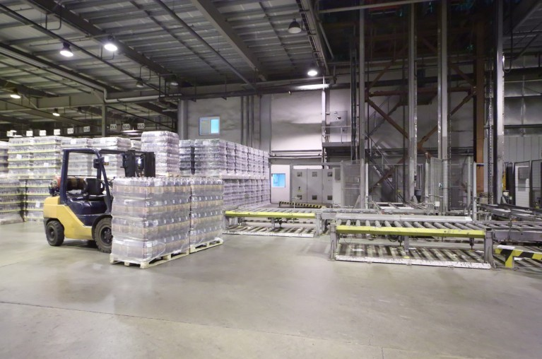 Lot of packaged beer bottles in large warehouse and loader machi